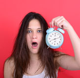 Portrait of sleepy young female in chaos holding clock against r Royalty Free Stock Photo
