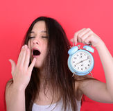Portrait of sleepy young female in chaos holding clock against r Stock Images