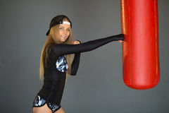 Portrait of a slender beautiful girl. Hitting a boxing leather red boxing pear Royalty Free Stock Images