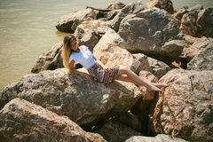 Portrait of slender young woman on stones near the sea Stock Photography
