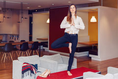 Portrait of slim fit sporty young white Caucasian business woman meditating doing yoga exercises Royalty Free Stock Photography