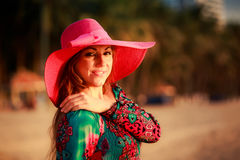 Portrait of slim girl in big red hat on beach. Portrait of slim brunette longhaired girl in colorful dress and big red hat on beach against palm trees Stock Photo