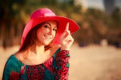 Portrait of slim girl in big red hat on beach Stock Image