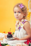 Portrait of slyly smiling girl posing with cake Royalty Free Stock Images