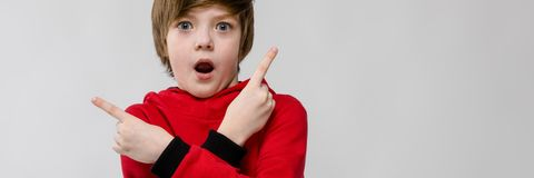 Cute confident funny surprised little caucasian boy with open mouth in red sweater on grey background. Portrait of small adorable thinking stylish confident royalty free stock photo