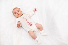 Portrait of small baby girl in her white bed. Portrait of small cute baby girl in her white bed royalty free stock image