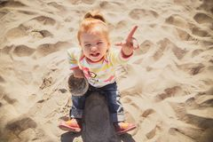 Portrait of small baby, little girl in blue jeans, pink shoes and colourful pullover sitting and playing in sand at the beach. Top view Royalty Free Stock Image