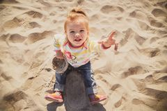 Portrait of small baby, little girl in blue jeans, pink shoes and colourful pullover sitting and playing in sand at the beach, top Stock Image