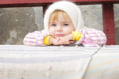 Portrait of the small beautiful girl. In a white scarf on a bench Royalty Free Stock Photo