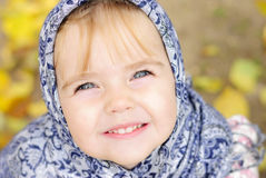 Portrait of the small beautiful girl. In a dark blue scarf Royalty Free Stock Photography
