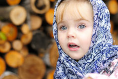 Portrait of the small beautiful girl. In a dark blue scarf Stock Photo