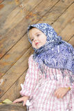 Portrait of the small beautiful girl. In a dark blue scarf bent on a fence Stock Image