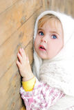 Portrait of the small beautiful girl in. A white scarf bent on a fence Royalty Free Stock Images