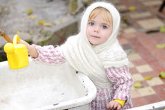 Portrait of the small beautiful girl. In a white scarf with a watering can Stock Photo