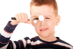Portrait of small boy. Child considers through magnifying glass world around, is isolated on white background Royalty Free Stock Images