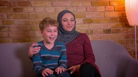 Portrait of small boy and his muslim mother in hijab hugging and watching TV together sitting on sofa at home. stock video
