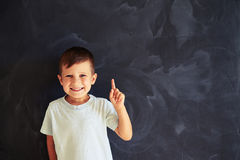 Portrait of small boy showing forefinger against school blackboa Stock Photos