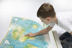 Portrait of small boy studying the map of the world Stock Photos