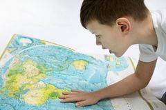 Portrait of small boy studying the map of the world Royalty Free Stock Image