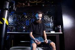 Portrait of small business owner of young man with beard. Guy bicycle mechanic workshop worker sitting with tool in his hand in a. Working black clothes in an stock image