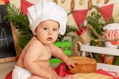 Portrait of a small child in a cook`s costume sitting among flour products and vegetables in the kitchen