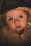 Portrait of a small child in the light of a candle. A cute baby. A cute baby. Sunlight on the child`s face. A curious look of a little girl. Sad look of the Royalty Free Stock Photos