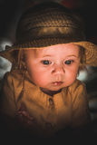 Portrait of a small child in the light of a candle. A cute baby. A cute baby. Sunlight on the child`s face. A curious look of a little girl. Sad look of the Stock Photos