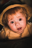 Portrait of a small child in the light of a candle. A cute baby. A cute baby. Sunlight on the child`s face. A curious look of a little girl. Sad look of the Royalty Free Stock Image