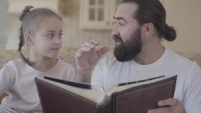 Portrait of small cute daughter and her father sitting in living room and looking photo album with good memories and. Funny stories stock video footage