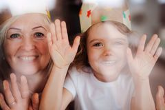 A portrait of small girl with grandmother having fun at home. Shot through glass. royalty free stock photos