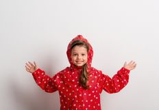 Portrait of a small girl with red anorak in studio on a white background. Portrait of a small girl with red anorak in studio on a white background, arms royalty free stock photos