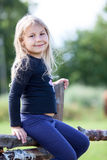 Portrait of small girl sitting on village fence Stock Images