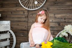 Portrait of a small girl in a spring studio. Portrait of a sad small girl in a spring studio. Rustic decor royalty free stock image