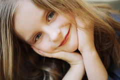 Portrait of small happy girl with long blond hair. Royalty Free Stock Images