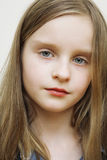 Portrait of small happy girl with long blond hair. Stock Photos