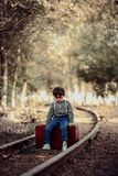 Portrait of a small and very cute boy dressed in retro style, sitting on a vintage suitcase on an abandoned railway and taking pho royalty free stock image