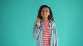 Portrait of smart African American woman having great idea raising finger. And smiling looking at camera standing on blue background. People and gestures stock video footage