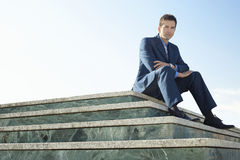 Portrait Of Smart Businessman Sitting On Marble Staircase Stock Photography