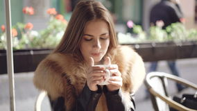 Portrait of smart girl drinking a cup of hot coffee in cafe. 4K stock video footage