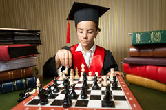 Portrait of smart girl in graduation cap playing chess. Closeup portrait of smart girl in graduation cap playing chess Royalty Free Stock Photo