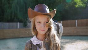 Portrait of a smart happy girl looking at camera at the horse area. 4K stock footage