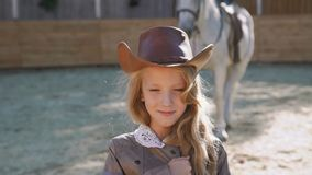 Portrait of a smart happy girl smiling at camera at the horse area. 4K stock video footage
