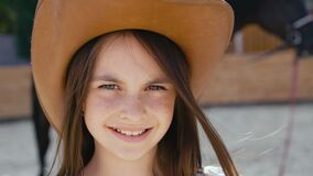 Portrait of a smart happy girl smiling at camera at the horse area. 4K stock footage