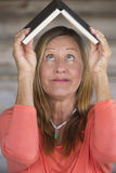Portrait smart happy woman with book on head Stock Images