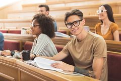 Cheerful male student sitting at lecture hall. Portrait of smart happy young men reading textbook on seminar. He is looking at camera and smiling Royalty Free Stock Photos