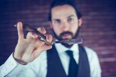 Portrait of smart hipster holding razor Stock Photo