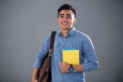 Smart looking male student. Portrait of smart looking male student with his books and bag Royalty Free Stock Photos