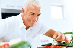 Portrait of a smart senior man cooking in kitchen. Portrait of a smart senior man making salad in kitchen royalty free stock image