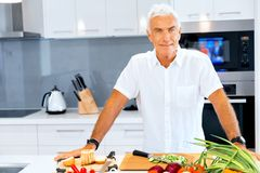 Portrait of a smart senior man standing in kitchen. Portrait of a smart senior man with standing in kitchen royalty free stock images