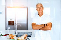 Portrait of a smart senior man standing in kitchen. Portrait of a smart senior man with standing in kitchen stock images